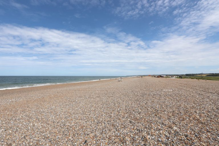 The pebble beach at Cley under a big blue sky.