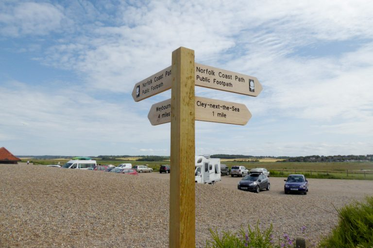 Wooden signpost at Cley beach car park.