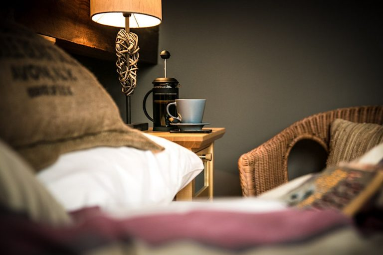 Cafetiere and coffee cup on a bedside table.