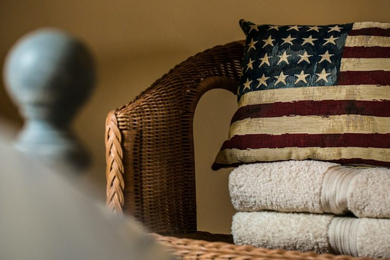 A cushion and some towels on a chair at Cog Cottage.