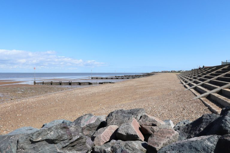 Rocks, wooden groynes and concrete steps at Heacham beach.
