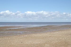 An empty beach and clouds in the sky at Heacham.