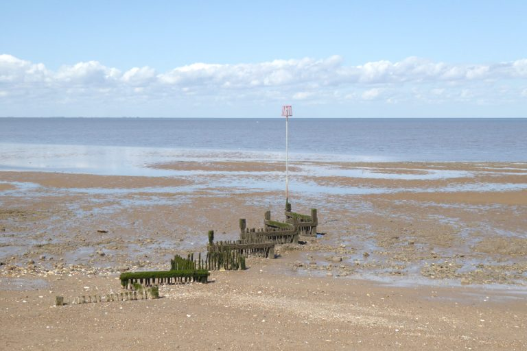 A wooden groyne during low tide at Heacham beach.