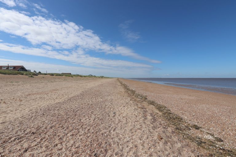 The sand and shingle beach under a blue sky at Heacham.