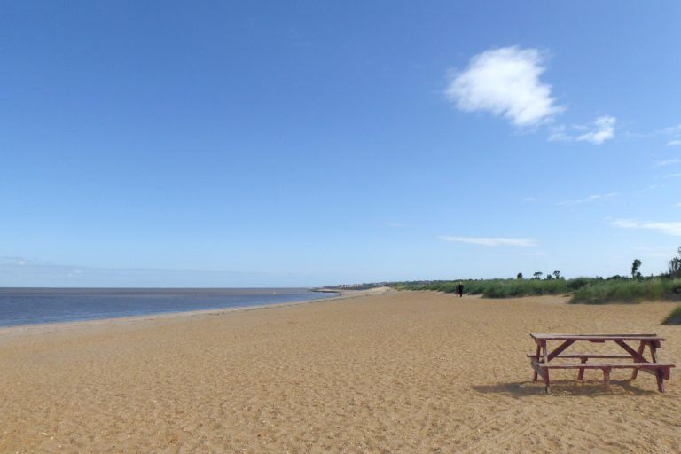 A sandy beach with picnic table under a blue sky at Heacham.
