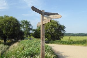 A wooden signpost at Holkham showing directions and facilities.