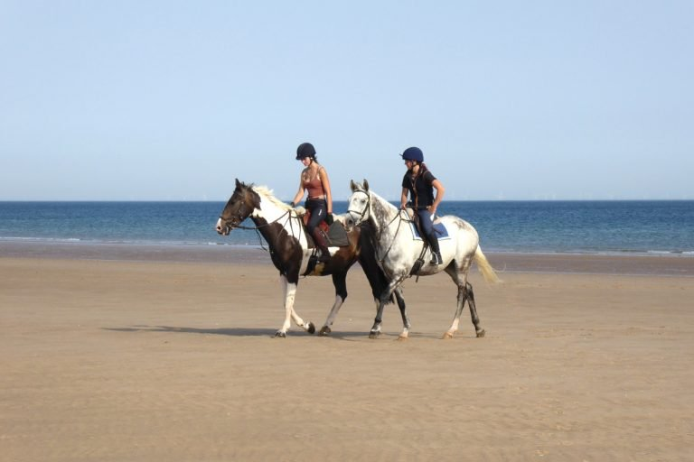 Two horse riders on the beach at Holkham in Norfolk.