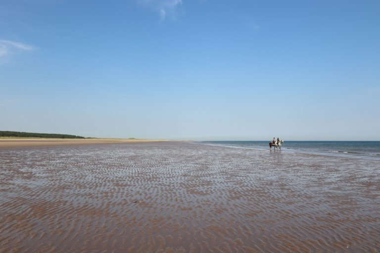 Two horse riders on the shore at Holkham beach.