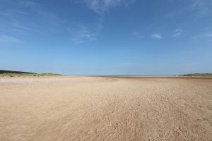 The vast beach at Holkham under a blue sky.