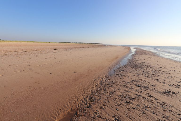 An empty sandy beach with distant dunes at Holme.