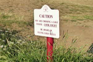 Caution sign in the grass at Hunstanton golf course.
