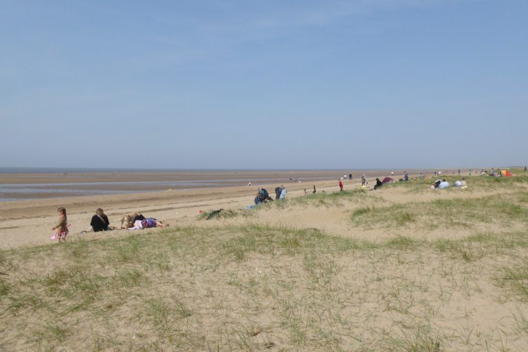 People enjoying the sandy north beach at Hunstanton.