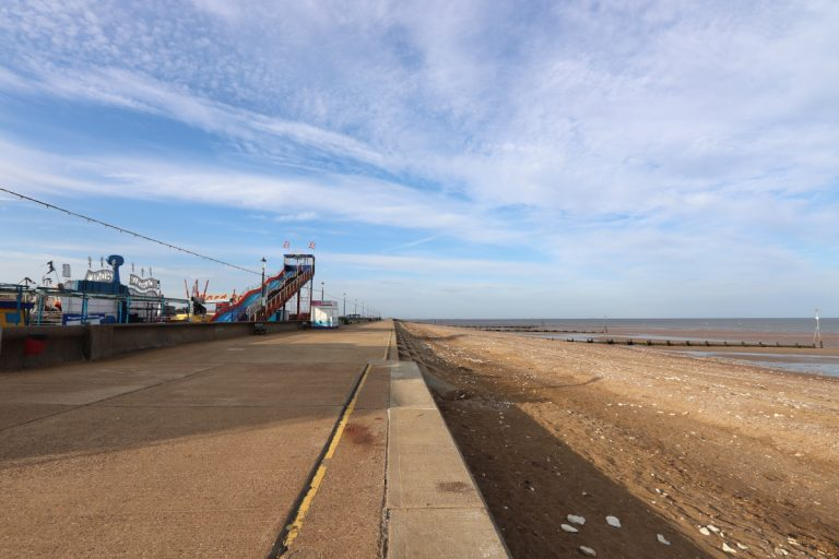 The seafront promenade at Hunstanton with distant funfair rides and giant slide.
