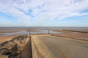 The concrete slipway bordered by rocks and the beach at low tide at Hunstanton.