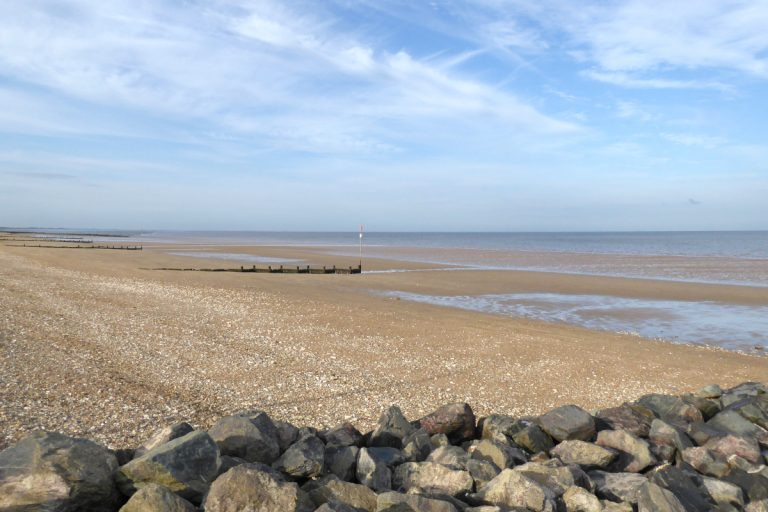 An empty South Hunstanton beach with wooden groynes and rocks.