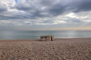 The concrete pillbox at Kelling beach under a dramatic sky.