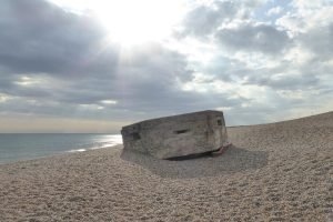 A concrete military pillbox on Kelling beach as the sun breaks out.