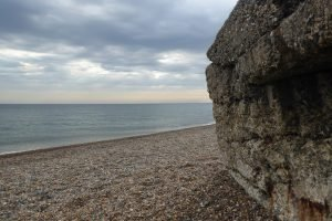 Close-up of military pillbox on Kelling beach with a moody sky.