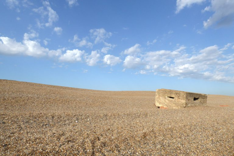 A military pillbox partially buried in the pebbles on Kelling beach.