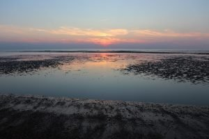 Pink sunset reflected in the water at Hunstanton beach.