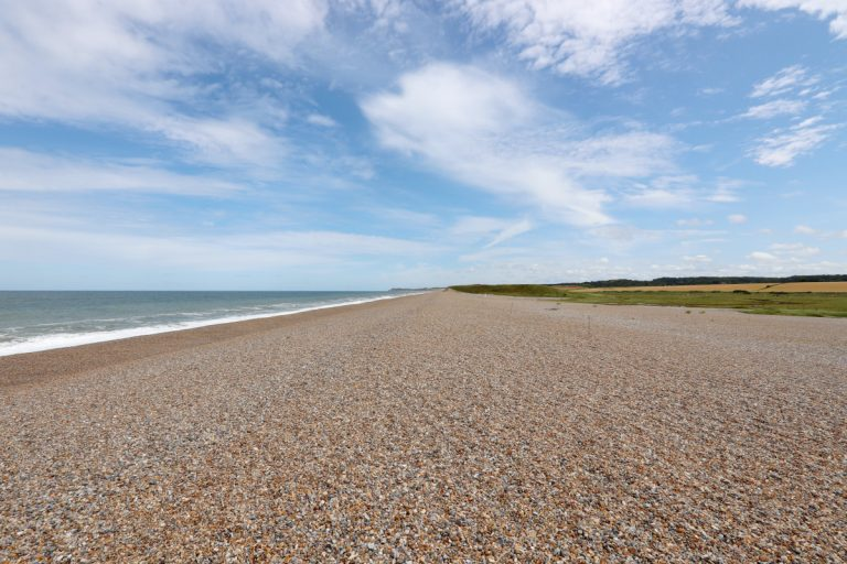 The pebble beach under a blue sky at Salthouse.