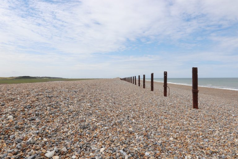 Pebbles and metal posts on the beach at Salthouse.