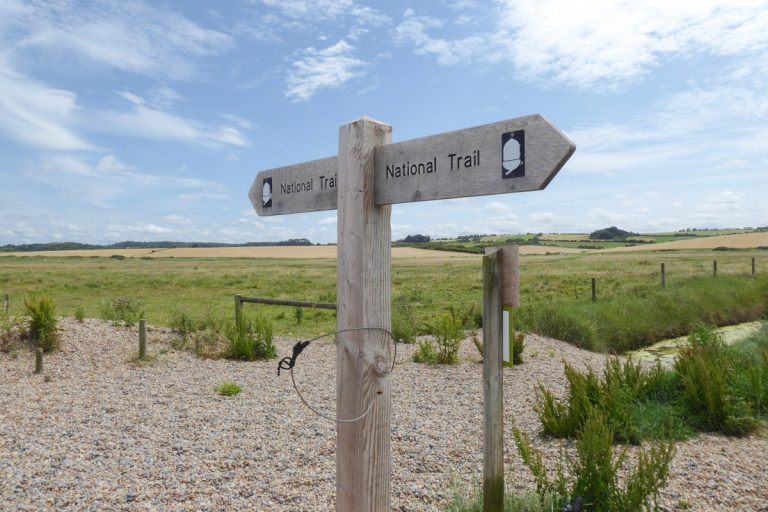 Wooden National Trail signpost at Salthouse beach.