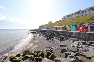 A row of colourful beach huts on the promenade at Sheringham.