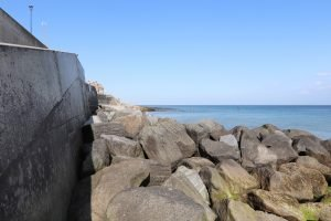 Large rocks on Sheringham beach with a blue sea behind.