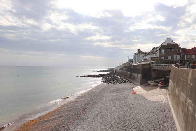 The beach at Sheringham with seafront promenade buildings.