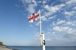 The RNLI flag flying against a blue sky with fluffy clouds.