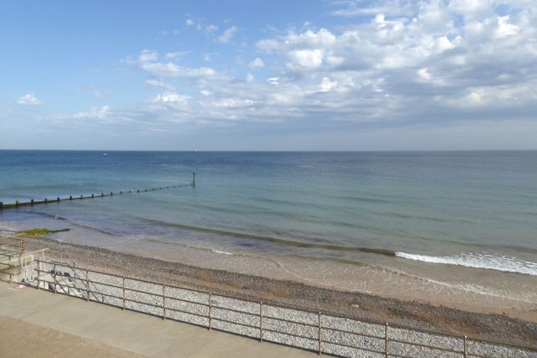 Sheringham beach at high tide on a sunny day.