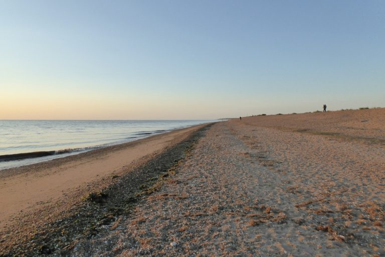 Walkers on the beach as the sun sets at Snettisham.
