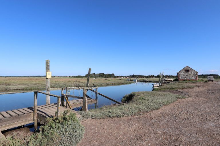 The old coal barn at Thornham harbour under a blue sky.