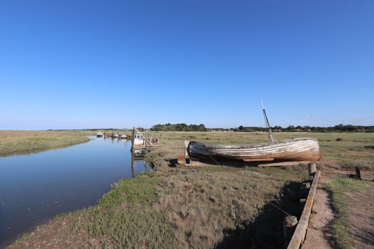Boats at Thornham harbour under a blue sky.