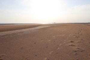 Footprints in the sand on an empty beach at Titchwell.