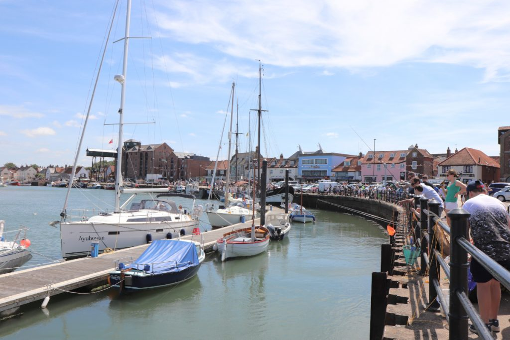 The harbour in Wells with holidaymakers crabbing off the quay.