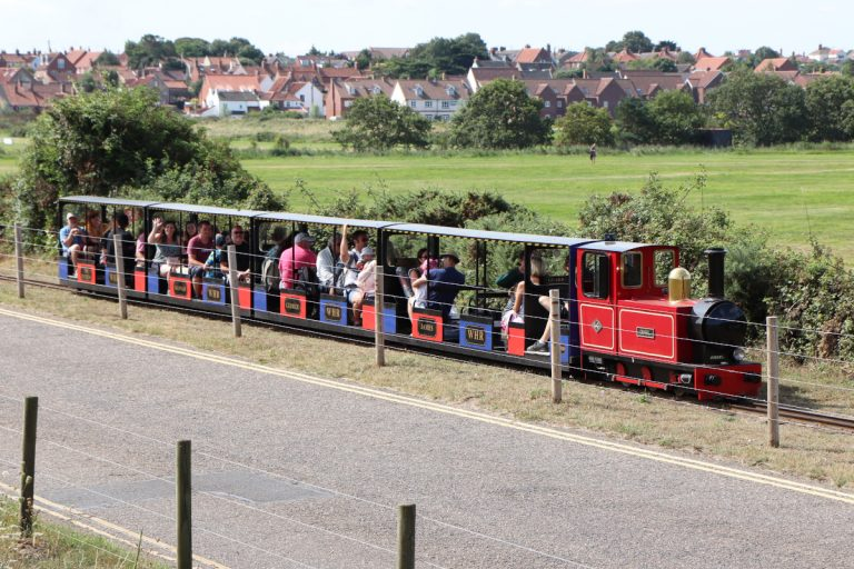 The Wells Harbour Railway travelling between the town and the beach at Wells-next-the-Sea.
