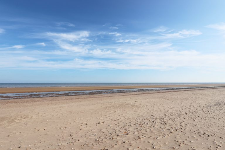 The vast sandy Holme beach with big blue sky and wispy clouds.