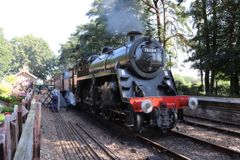 A steam engine puffing smoke at Holt Station.