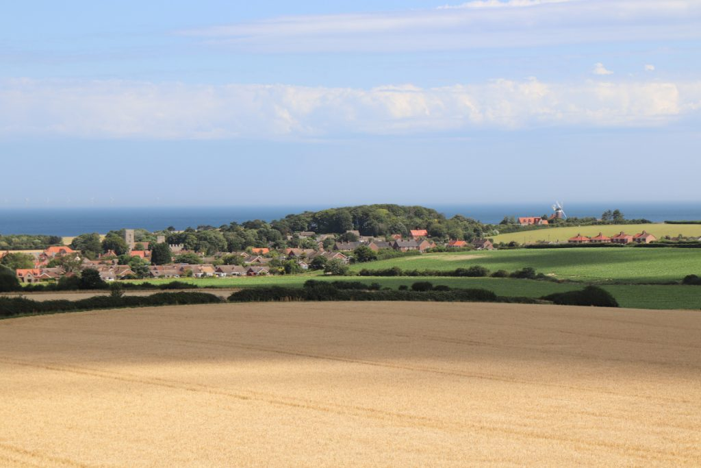 Distant view of Weybourne including the church and windmill.