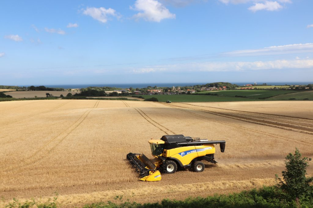 A combine harvester in the fields with Weybourne in the distance.