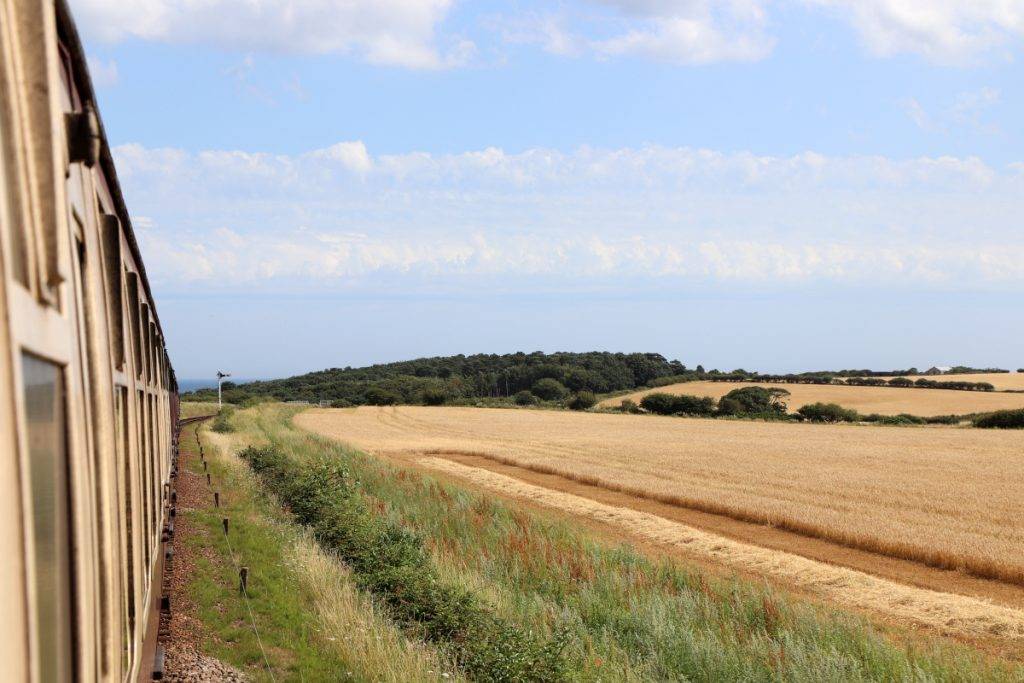 View of golden fields and trees from the North Norfolk Railway.