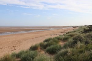 The empty beach during low tide at Old Hunstanton with marram grass in the dunes.