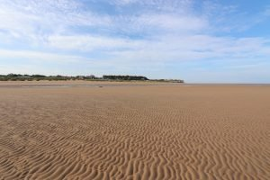 Old Hunstanton beach at low tide with the famous cliffs and lighthouse in the distance.