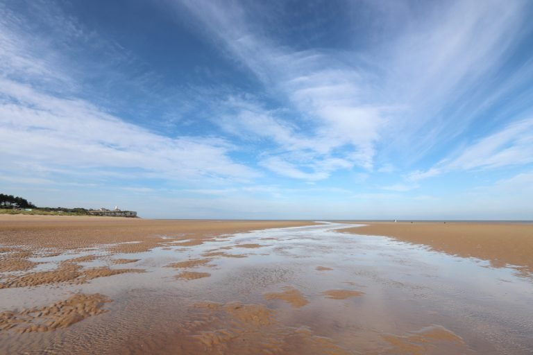 The vast empty beach at Old Hunstanton with a big blue sky and distant lighthouse.