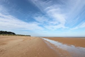 A vast expanse of beach at Old Hunstanton with the lighthouse in the distance.