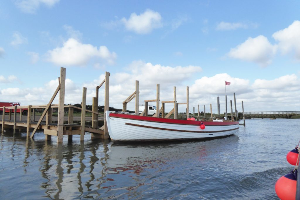 An empty wooden seal trip boat moored alongside a jetty at Morston Quay.