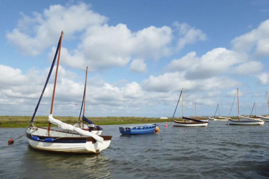 Small wooden fishing boats anchored at Morston Creek in Norfolk.