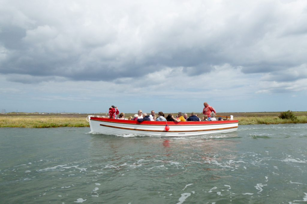 A boat carrying passengers in the water on a Blakeney Point seal trip.